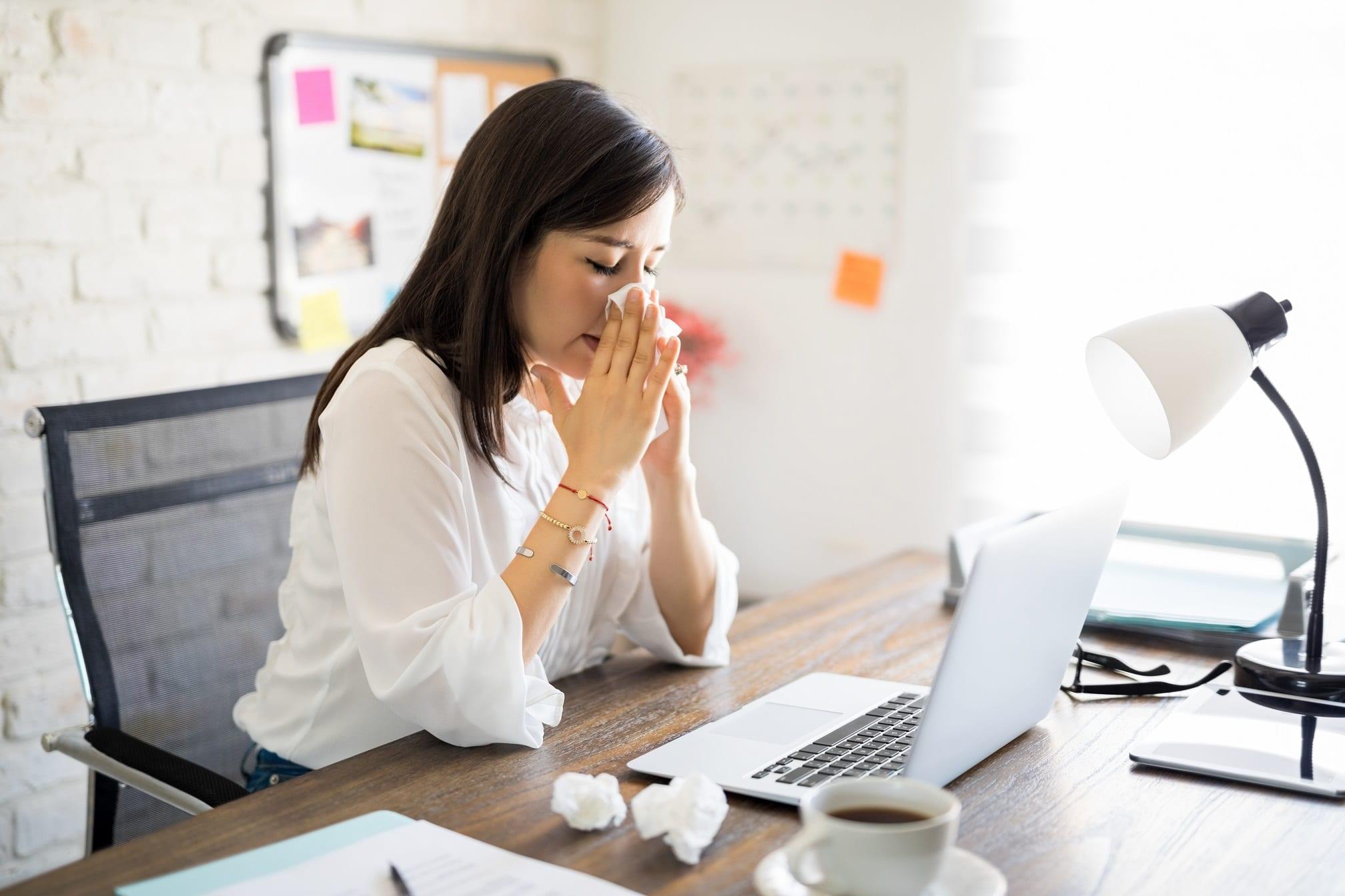 businesswoman blowing into tissue ill flu coronavirus